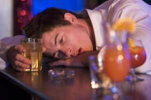 Drunk young man resting head on bar counter